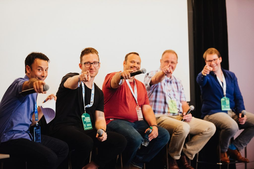 Presenters point their microphones at the camera during a break
