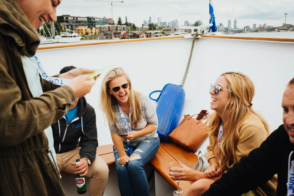 TUNE marketers laugh on a boat ride on Lake Washington