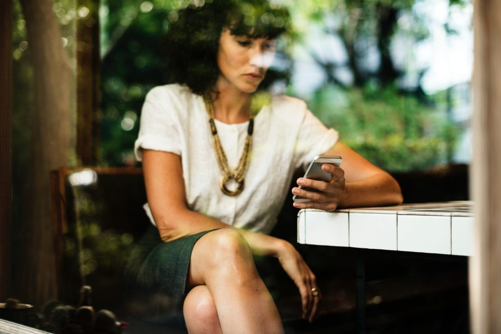 A woman looks at her phone in preparation for GDPR's affect on programmatic advertising.
